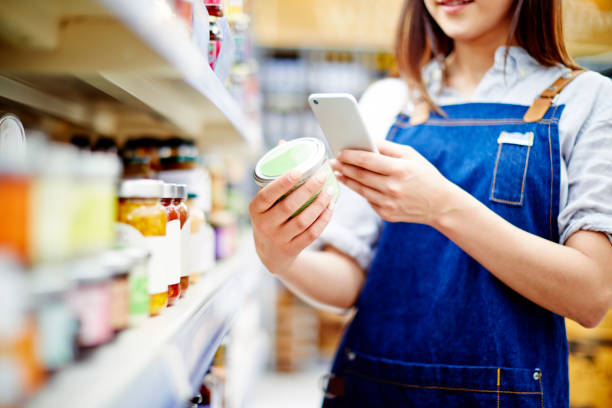 Deli owner scanning label on food container with smart phone stock photo