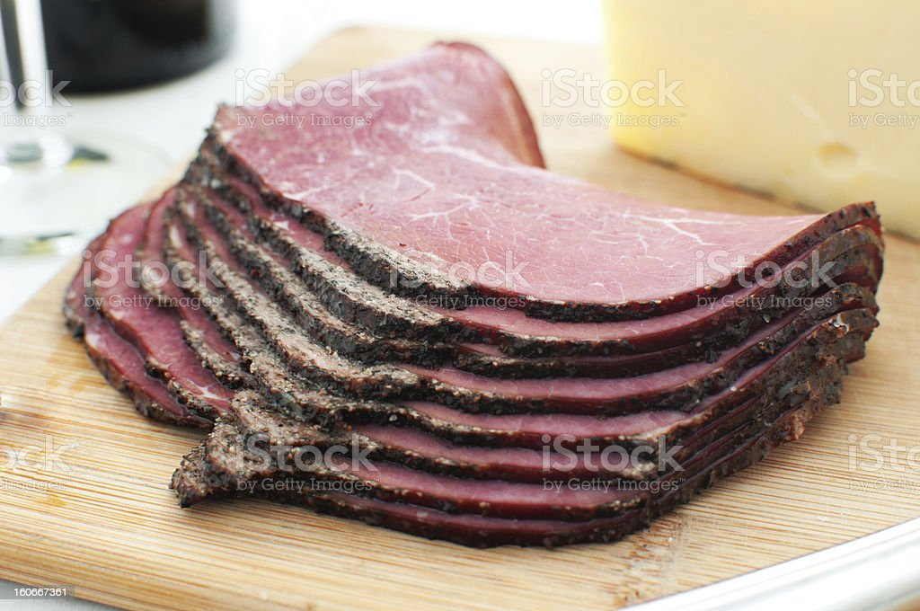 Deli pastrami meat sliced on cutting board stock photo