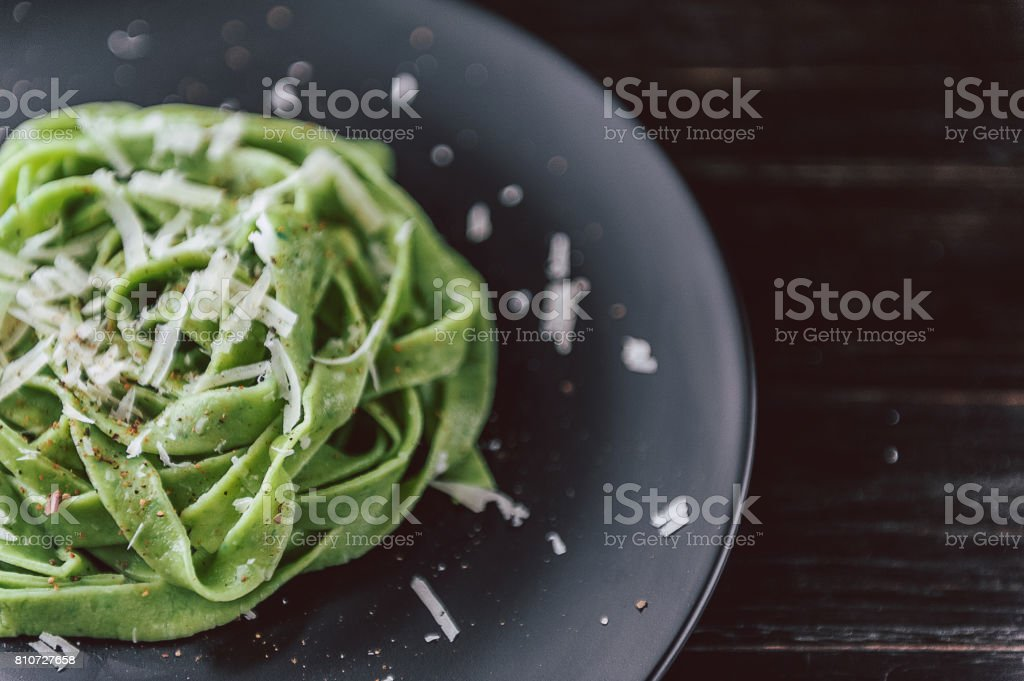 delicacy green pasta with homemade spinach and broccoli under a parmesan cheese and sesame seeds stock photo