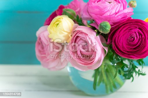Beautiful ranunculus (buttercup) in vase on rustic wooden background