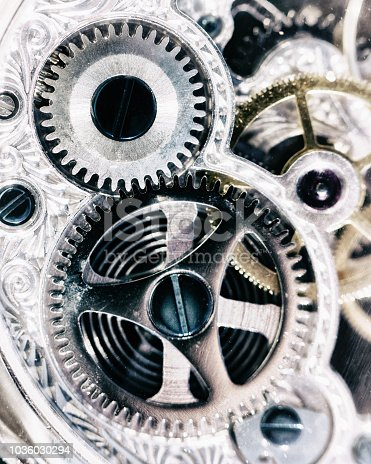 Looking down at a close-up of the complex inner workings of a watch or clock.