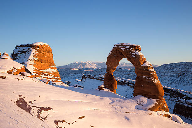 Delicate Arch at sunset in Winter Wide angle view of Delicate Arch in Winter at Arches National Park in Utah delicate arch stock pictures, royalty-free photos & images