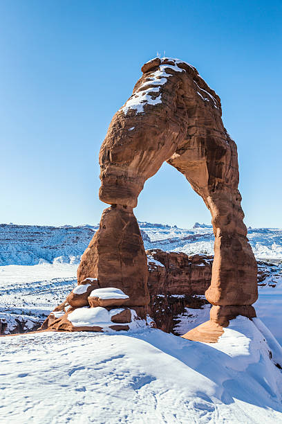 Delicate Arch Hoodoo Rock - Arches National Park Utah USA Delicate Arch, the iconic, weathered, eroded, sandstone hoodoo rock formation at Arches National Park near Moab, Utah, in western USA. Shot taken in early February. Winter snow covers the base of the arch and the vallery and mountains in the background. delicate arch stock pictures, royalty-free photos & images