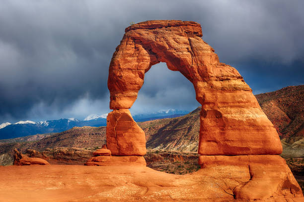 Delicate Arch Late evening photo of a Delicate Arch with a dramatic stormy sky in the back. Arches National Park, Utah - USA delicate arch stock pictures, royalty-free photos & images