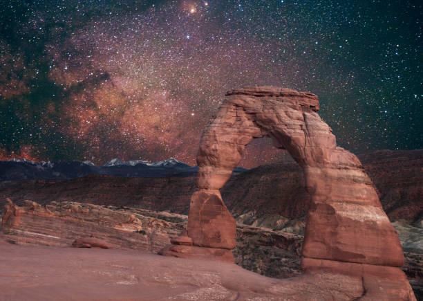 Delicate Arch with Milky Way Arches National Park Utah Night This is a color photograph of landmark, Delicate Arch in Arches National Park in Utah, USA at night with the Milky Way in the sky. The high desert landscape is full of rock formations created by erosion in sandstone over time. delicate arch stock pictures, royalty-free photos & images