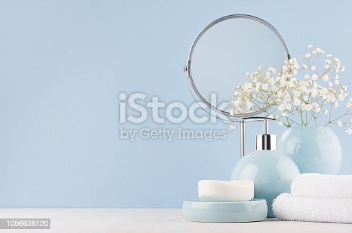 1056636898 istock photo Delicate elegant ceramic decorations for bathroom - soft blue bowls, vase, white flowers, towel and soap on white wood table. Modern bath interior. 1056636120