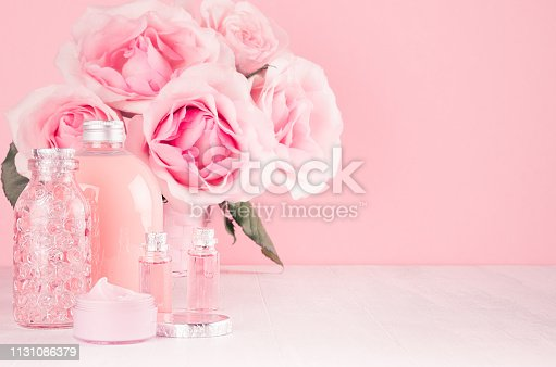 1056636898 istock photo Delicate girlish dressing table with bouquet of roses, cosmetic products for body and skin care in pastel pink color on white wood board, copy space. 1131086379