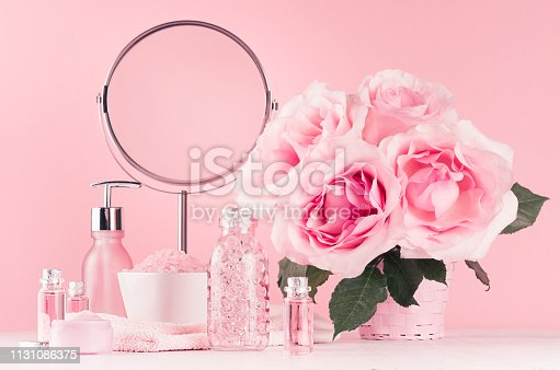 1056636898 istock photo Delicate girlish dressing table with bouquet of roses, round mirror, cosmetic products for body and skin care in pastel pink color on white wood board. 1131086375