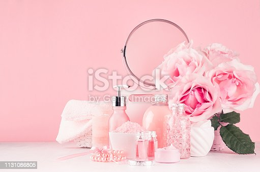 1056636898 istock photo Delicate girlish dressing table with bouquet of roses, round mirror, cosmetic products for body and skin care in pastel pink color on white wood board, copy space. 1131086805
