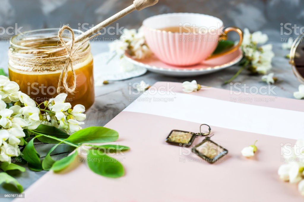 Delicate glass earrings in rustic style with a plant inside. Among the magazine, tea, honey - attributes for woman relaxation stock photo