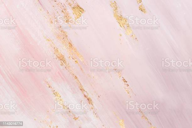 Photo of Delicate pink marble background with gold brushstrokes. Place for your design
