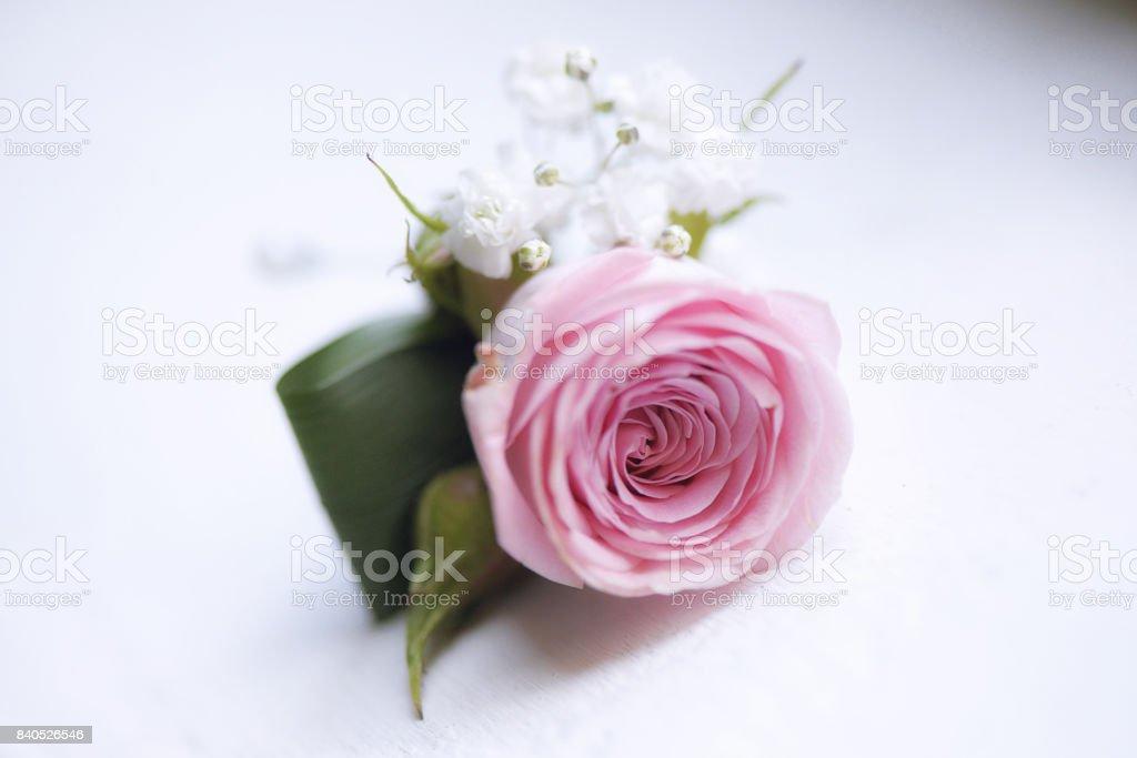 Delicado bouquet pequeño rosa rosa para ojales utilizado para novio y novia colocada contra un fondo blanco - foto de stock