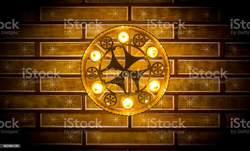 A delicate round chandeliers on a wooden support on the ceiling. stock photo