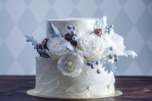Delicate white bunk wedding cake decorated with an original design using mastic roses. Concept of festive desserts