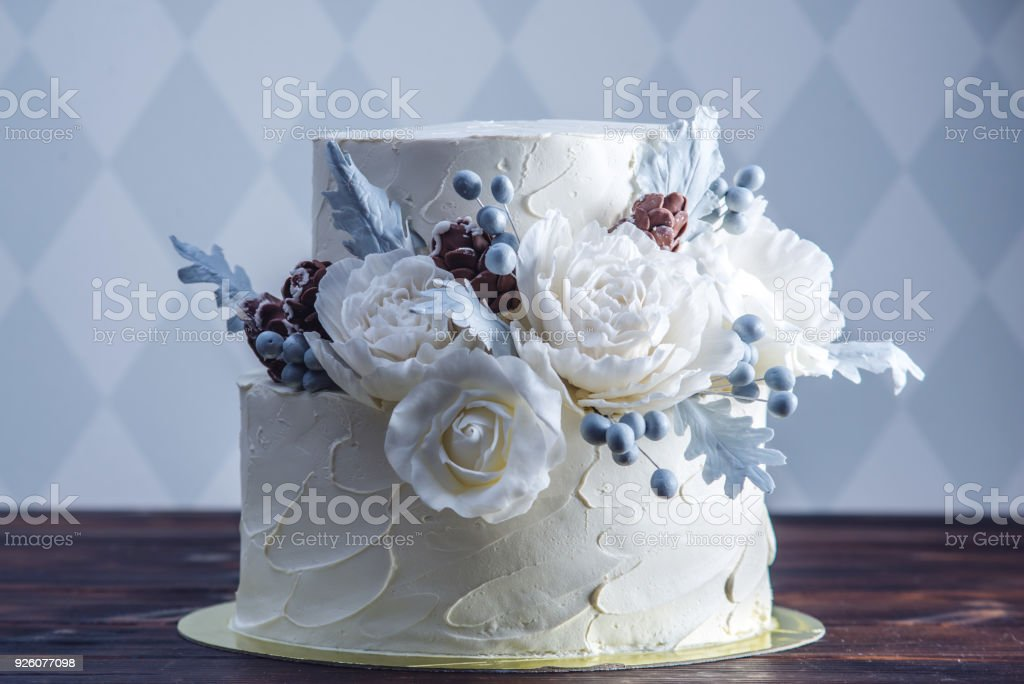 Delicate white bunk wedding cake decorated with an original design using mastic roses. Concept of festive desserts stock photo