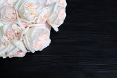 istock Delicate white roses on black wooden background closeup, beautiful light pink flowers bouquet on dark wood, birthday greeting card, valentines day, floral corner border, wedding frame, text copy space 1287161060