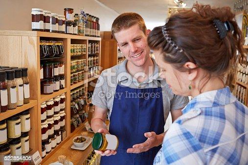 istock Delicatessen shop assistant advising customer 522854805
