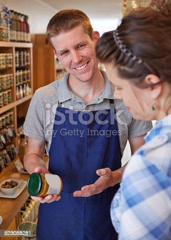 istock Delicatessen shop assistant advising customer 523088281