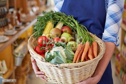 istock Delicatessen shop assistant holding basket of vegetables 522881371