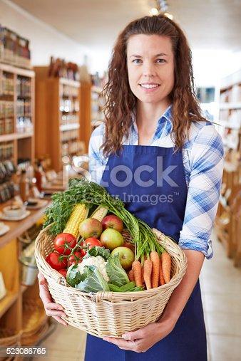 istock Delicatessen shop assistant holding basket of vegetables 523086765