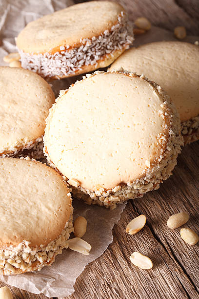 Delicious Alfajores cookies on paper close-up. Vertical, rustic - foto de stock