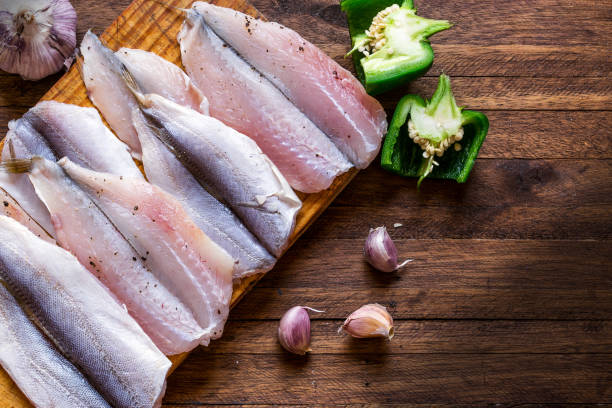 delicious and fresh, spiced and seasoned raw fish fillets on a cutting board, on top of a wooden background, with bell peppers, whole and garlic cloves as garnish - fish stock pictures, royalty-free photos & images
