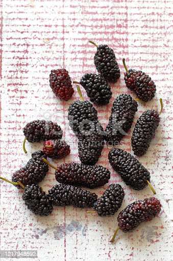 istock delicious and healthy mulberries on pink table 1217948592