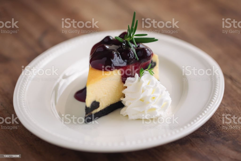Delicious And Sweet Blueberry New York Cheesecake On White Plate Served With Whipped Cream Wood
