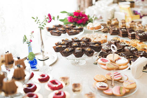 Delicious and tasty dessert table with cupcakes shots at reception stock photo
