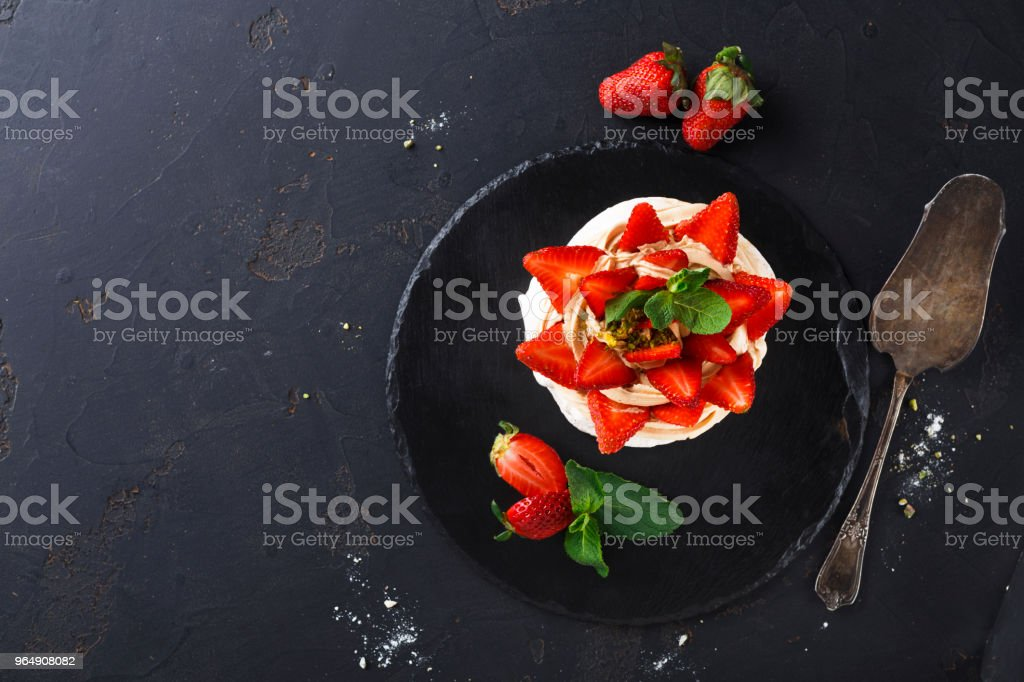 Delicious Anna Pavlova meringue cake with strawberry on black background royalty-free stock photo