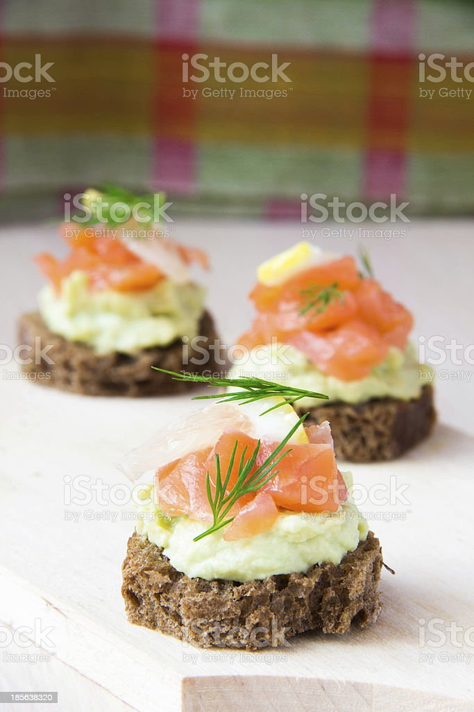 Delicious appetizer canapes of black bread, avocado and red fish royalty-free stock photo