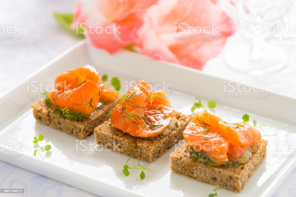 Delicious appetizer canapes of black bread with smoked salmon stock photo