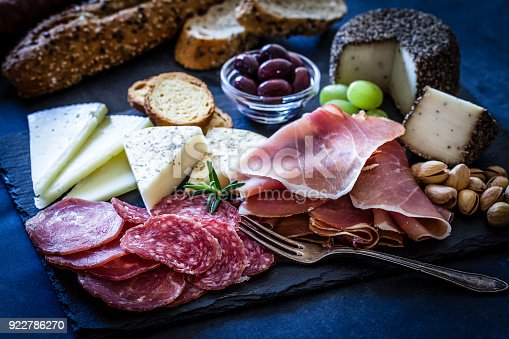 High angle view of a slate tray with a delicious appetizer shot on bluish tint background. The composition includes various types of cheese, Serrano ham, salami, black olives and crostini. Low key DSRL studio photo taken with Canon EOS 5D Mk II and Canon EF 100mm f/2.8L Macro IS USM