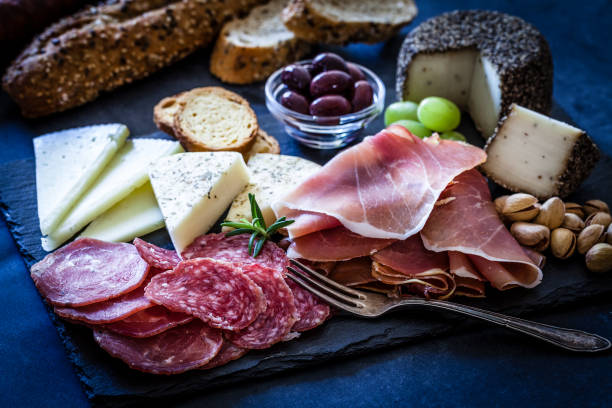 delicious appetizer on bluish tint table - delis stock photos and pictures