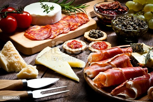 Rustic wood table filled with a assortment of fine food. A wood tray with prosciutto and cheese is at the bottom-right of the frame. Two glass bowls with dried tomatoes and olives paste and a cutting board are at the top. Various types of cheese complete de composition. DSRL studio photo taken with Canon EOS 5D Mk II and Canon EF 100mm f/2.8L Macro IS USM