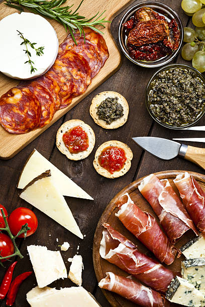 Delicious appetizer on rustic wood table Top view of a rustic wood table filled with a assortment of fine food. A wood tray with prosciutto and cheese is at the bottom-right of the frame. Two glass bowls with dried tomatoes and olives paste and a cutting board are at the top. Various types of cheese complete de composition. DSRL studio photo taken with Canon EOS 5D Mk II and Canon EF 100mm f/2.8L Macro IS USM iberian stock pictures, royalty-free photos & images