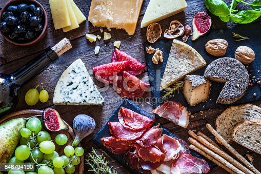 Top view of a rustic wooden table filled with delicious cheese and cold meat selection. Some fruits like figs, pears and grape and some nuts complete the composition. DSRL studio photo taken with Canon EOS 5D Mk II and Canon EF 100mm f/2.8L Macro IS USM