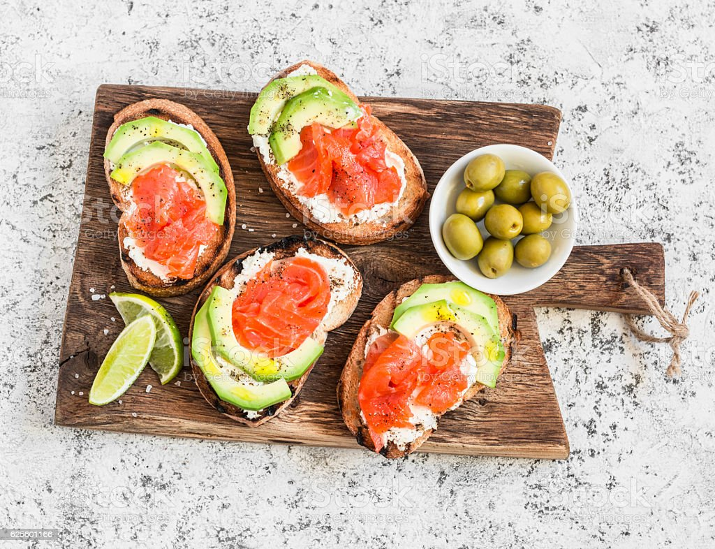 Delicious appetizers - cream cheese, smoked salmon and avocado sandwiches стоковое фото