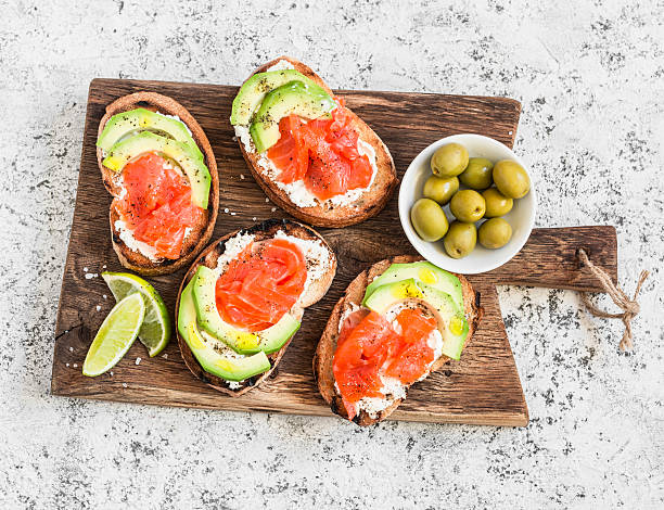 Delicious appetizers - cream cheese, smoked salmon and avocado sandwiches - foto stock