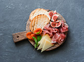 Delicious appetizers for wine or a snack - prosciutto, figs, bread, cheese on a rustic wooden cutting board. On a gray background, top view