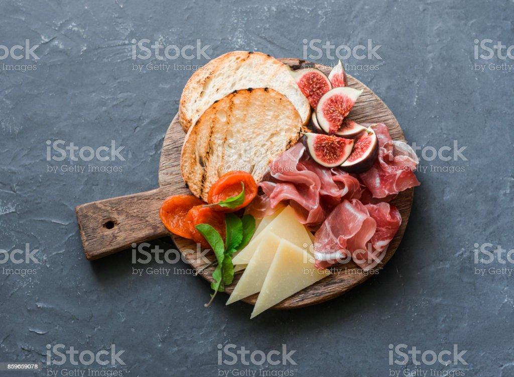 Köstliche Vorspeisen für Wein oder einen Snack - Feigen, Brot, Schinken, Käse auf einem rustikalen Holzbrett. Oben Sie auf einem grauen Hintergrund Ansicht von – Foto