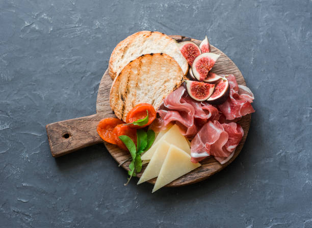 Delicious appetizers for wine or a snack - prosciutto, figs, bread, cheese on a rustic wooden cutting board. On a gray background, top view stock photo