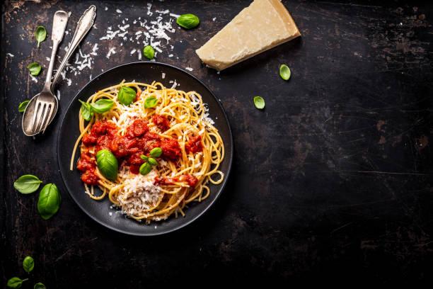delicious appetizing classic spaghetti pasta with tomato sauce, parmesan cheese and fresh basil, top view - macarrão imagens e fotografias de stock