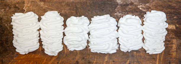 Delicious appetizing meringue on wooden background. meringues artisanales. French dessert with eggs, protein and sugar. stock photo
