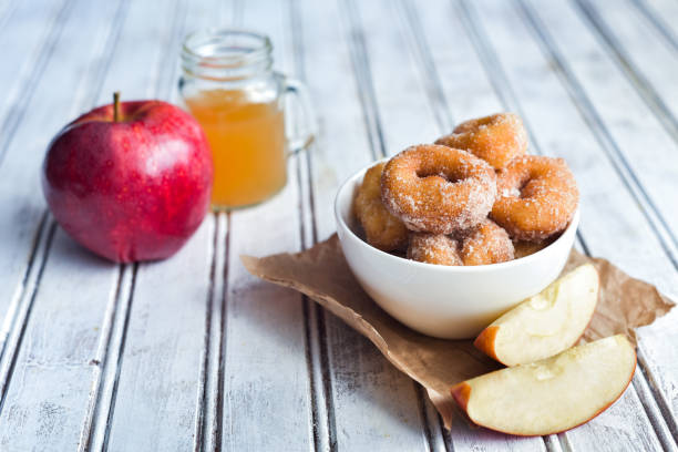 Delicious Apple Cider Donuts Sweet and savory apple cider donuts on a table. hot apple cider stock pictures, royalty-free photos & images