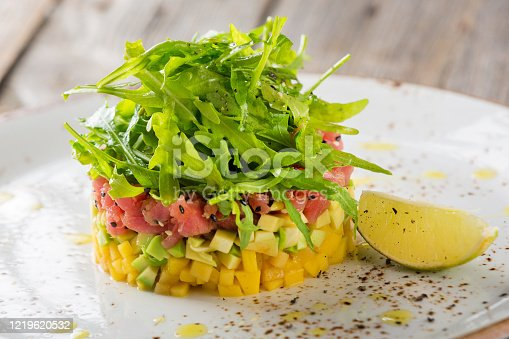 Delicious avocado, mango and raw salmon salad, tartare, served on a white plate with lime. Close-up