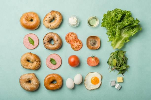leckere bagel-sandwiches - knolling - käse wurst salat stock-fotos und bilder