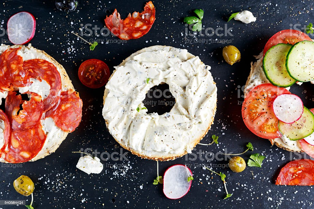 Delicious Bagel sandwiches with soft cheese, chorizo and vegetables stock photo