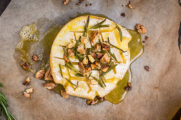 delicious baked camembert with honey, walnuts, herbs and pears - baked brie stock photos and pictures