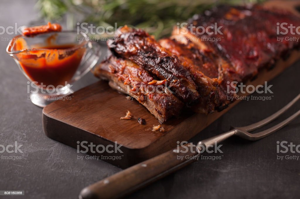 Delicious barbecued ribs seasoned with a spicy basting sauce and served with chopped fresh vegetables on an old rustic wooden chopping board in a country kitchen stock photo